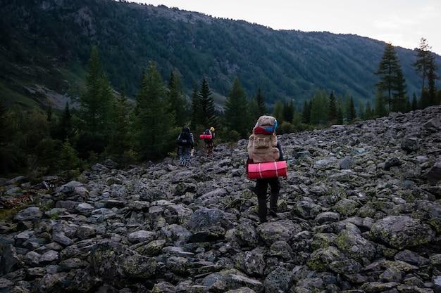 Viandante che sale in una montagna. turista con un grande zaino la sera si intrufola tra i depositi di pietra sul fianco della montagna.