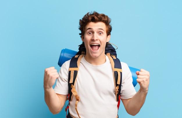 Ragazzo escursionista che si sente scioccato, eccitato e felice, ride e celebra il successo, dicendo wow!