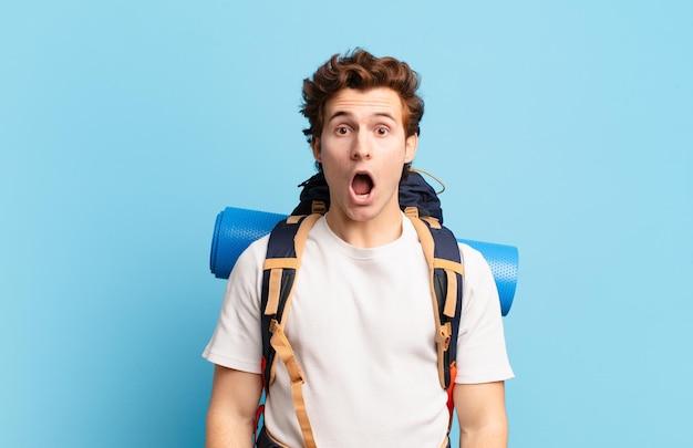Ragazzo escursionista che sembra molto scioccato o sorpreso, fissando con la bocca aperta dicendo wow