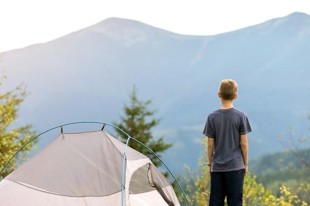 Bambino escursionista che riposa in piedi vicino a una tenda da campeggio in un campeggio di montagna che gode della vista della natura estiva.