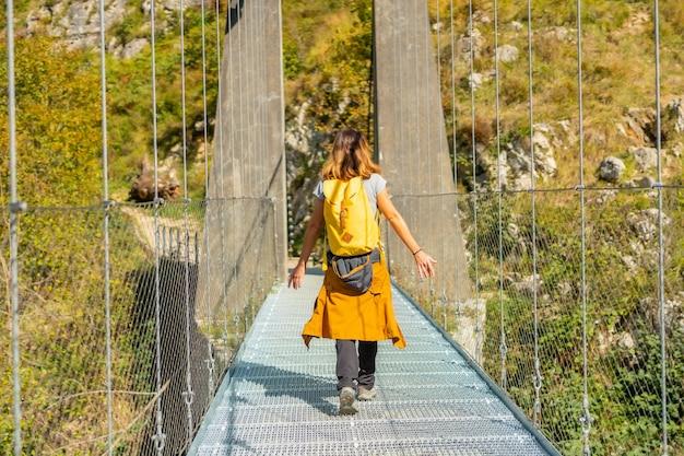Un escursionista che attraversa il ponte sospeso holtzarte, larrau. nella foresta o nella giungla di irati, pirenei atlantici della francia