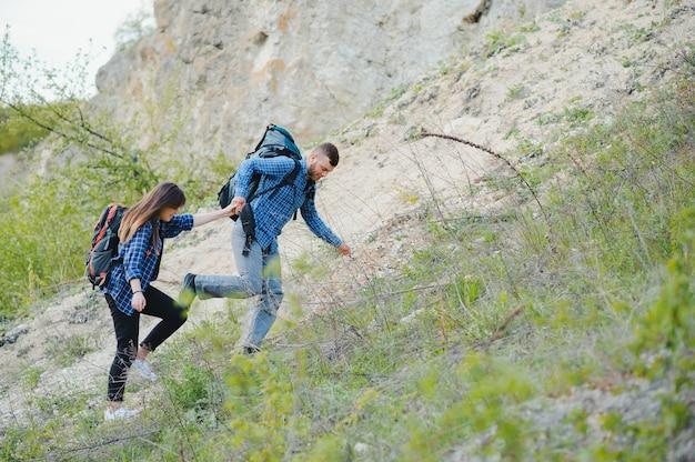 Ragazzo escursionista dà una mano alla ragazza mentre cammina in montagna