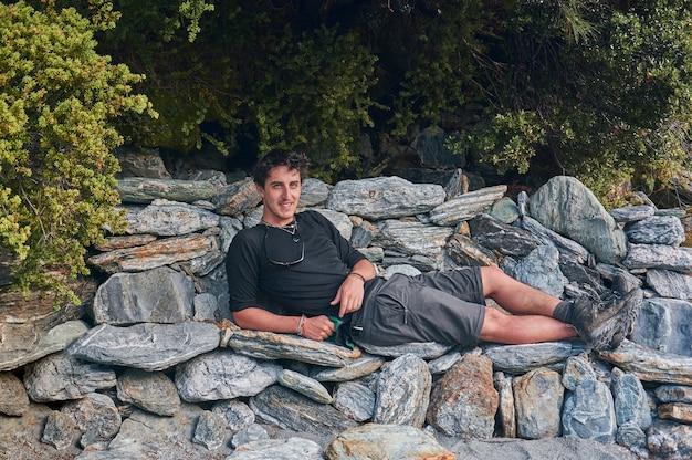 Ragazzo escursionista si rilassa su una panchina fatta di rocce in una foresta.