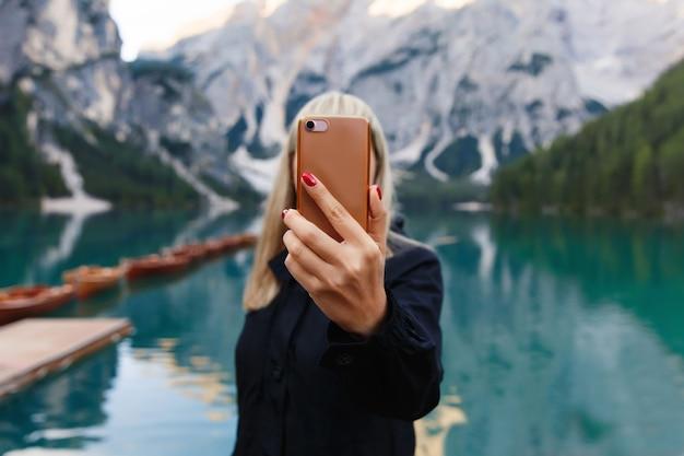La viandante fa la foto di bello paesaggio sullo smartphone