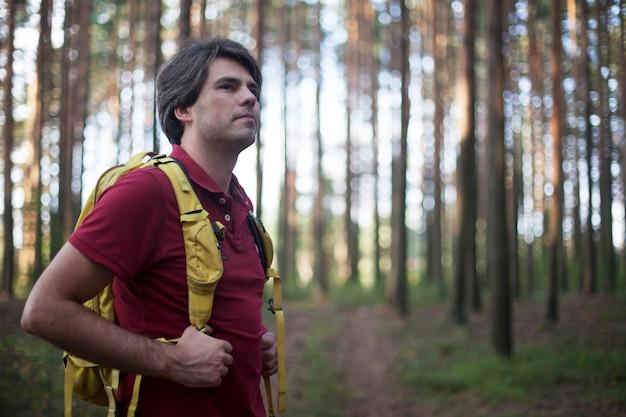 Viandante - uomo che fa un'escursione nella foresta. viandante maschio che guarda al lato che cammina nella foresta. modello maschio caucasico all'aperto in natura.