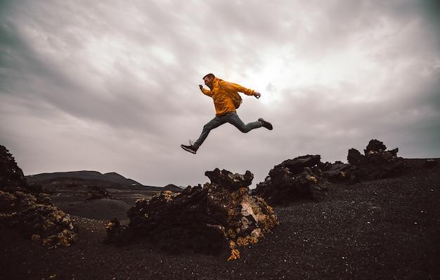 Uomo della viandante che salta sopra la montagna.