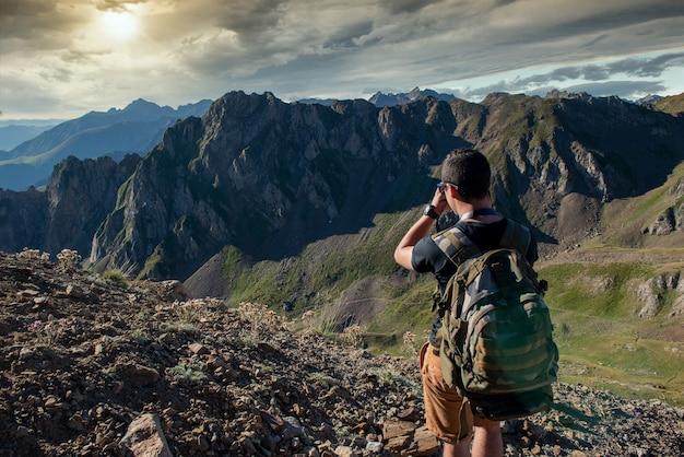 Uomo della viandante che cattura un'immagine delle montagne dei pirenei