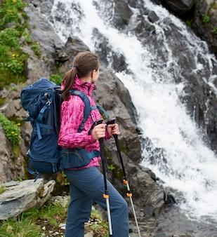 Viandante in attrezzatura moderna vicino alla cascata