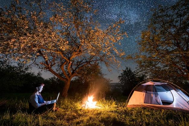Escursionista vicino al fuoco e tenda turistica di notte