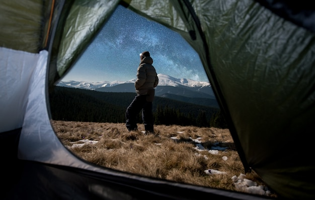 Escursionista vicino alla tenda turistica di notte