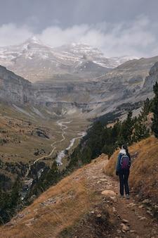Escursionista osservando una valle con un fiume e montagne dalle vette innevate