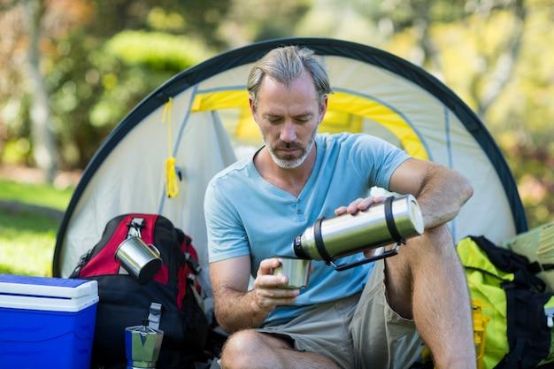 Escursionista versando acqua dalla bottiglia thermos
