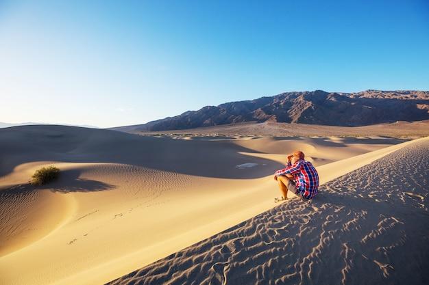 Escursionista nel deserto di sabbia. ora dell'alba. Foto Premium