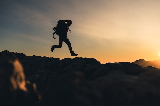 Escursionista in cima a una montagna correre sul crinale della montagna con un bellissimo tramonto dell'ora d'oro con colori intensi e cielo blu fuso con il giallo, porta un grande zaino