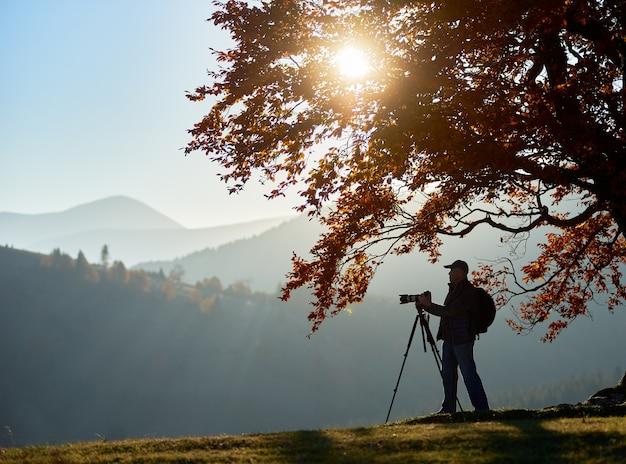 Uomo turistico escursionista con la macchina fotografica sulla valle erbosa sullo sfondo del paesaggio di montagna sotto il grande albero.