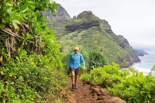 Escursionista sul sentiero nella giungla verde, hawaii, usa