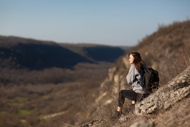 Escursionista con zaino seduto sul bordo della scogliera e godersi la vista sulla valle durante il percorso di trekking