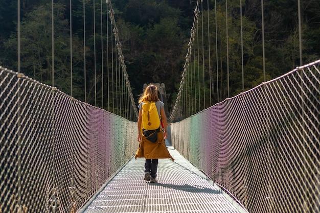 Un escursionista con uno zaino giallo che attraversa il ponte sospeso holtzarte, larrau. nella foresta o nella giungla di irati, pirenei atlantici della francia