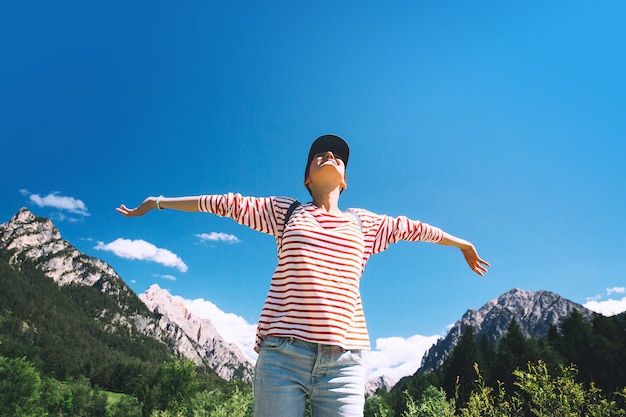 Escursionista donna con le braccia alzate sulla natura all'aperto vista posteriore viaggio nelle dolomiti italia europa