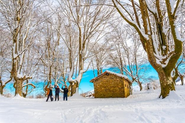 Escursionisti vicino al bellissimo rifugio tra alberi giganti nel parco naturale di oianleku nella città di oiartzun lungo penas de aya, gipuzkoa. paese basco