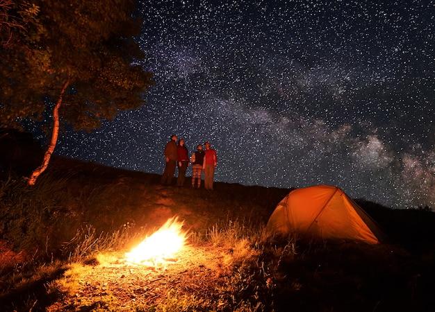 Escursionisti vicino al fuoco e tenda turistica di notte