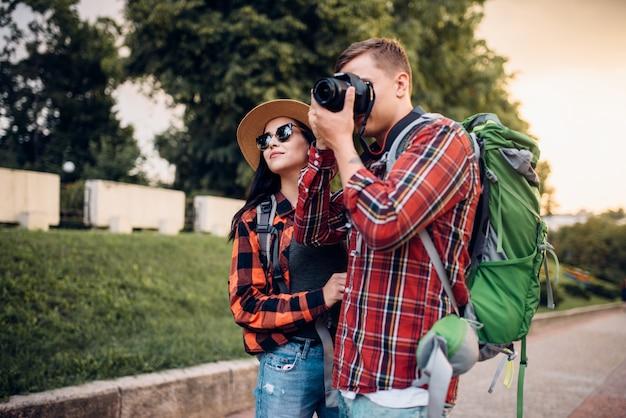 Gli escursionisti con gli zaini vanno in giro per la città turistica e fanno foto per ricordo. escursioni estive. escursione all'avventura di un giovane uomo e una donna