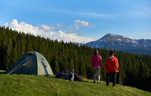 Escursionisti con zaini in cima a una collina vicino alle tende