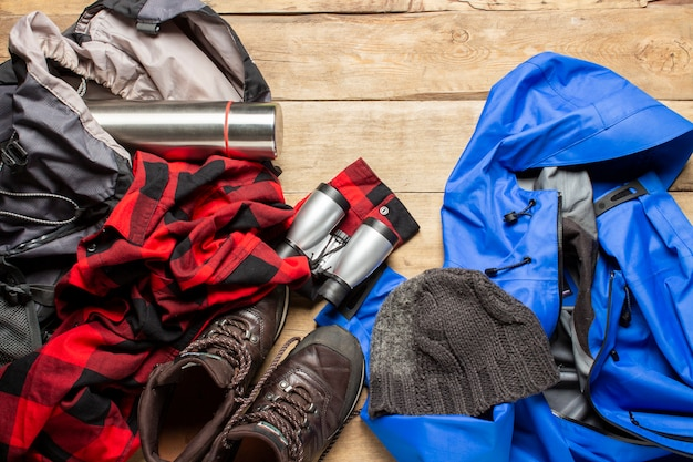 Scarponcini da trekking, giacca, binocolo, camicia, cappello, zaino su uno spazio di legno. il concetto di escursionismo, turismo, campeggio, montagne, foreste. bandiera