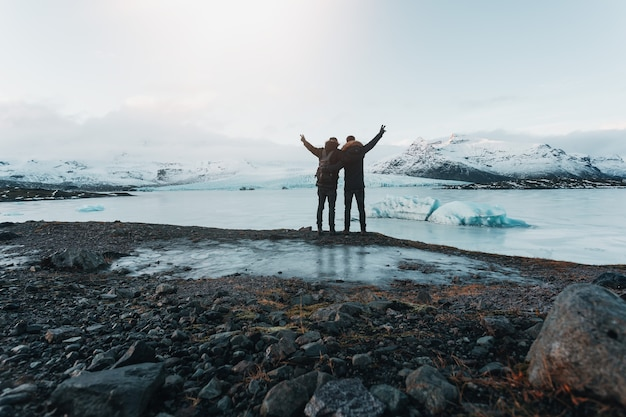 Escursionismo su un ghiacciaio in islanda, vista mozzafiato, il viaggiatore si erge su una pietra, i viaggiatori hanno raggiunto la loro destinazione, l'amicizia