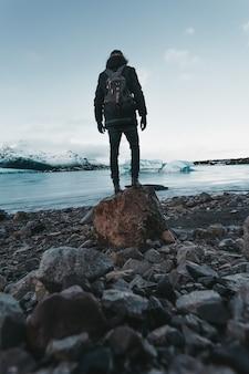 Facendo un'escursione su un ghiacciaio in islanda la vista mozzafiato del viaggiatore si erge sulla pietra