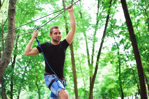 Facendo un'escursione nel parco della corda bello ragazzo di sport