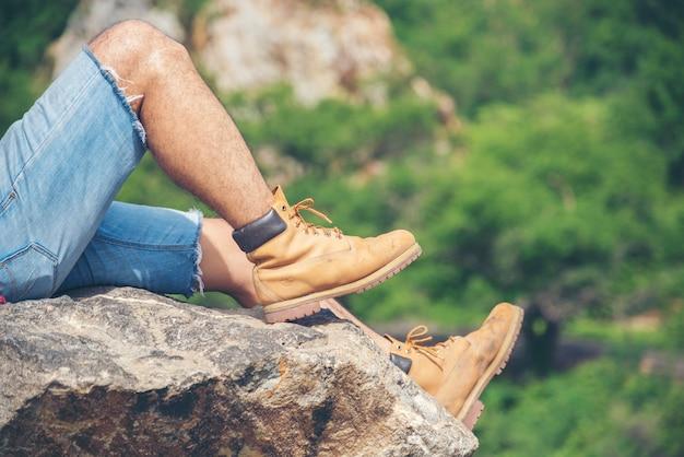 Escursionismo a piedi sulla montagna con esploratore di scarponi da trekking marroni su rock mountain view. concetto di stile di vita di libertà di viaggio dell'uomo di avventura.