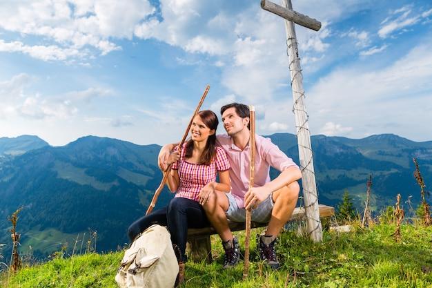 Escursionismo - giovane coppia seduta sulla cima della montagna all'incrocio delle alpi bavaresi e gode del panorama nel tempo libero o in vacanza