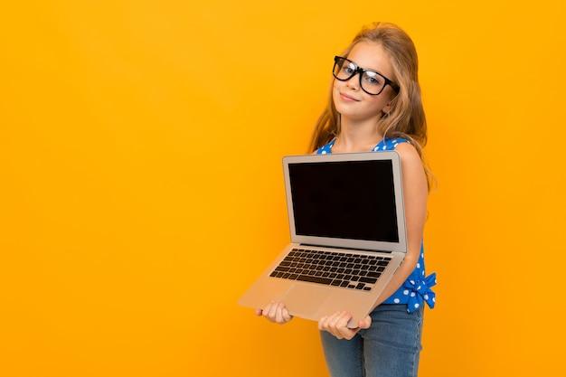Ragazza intelligente esilarante con un computer portatile su uno sfondo giallo