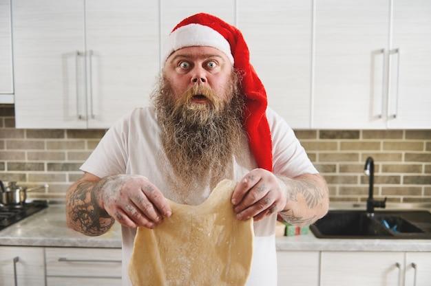 Uomo barbuto esilarantemente sorpreso in cappello rosso della santa e braccia tatuate che tengono pasta arrotolata nelle mani.