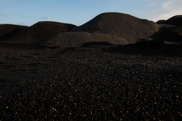 Colline di terreno scuro inquinato, sterile e tossico in tutto un vasto territorio con una cattiva situazione ambientale con cielo blu sopra e nessuno intorno