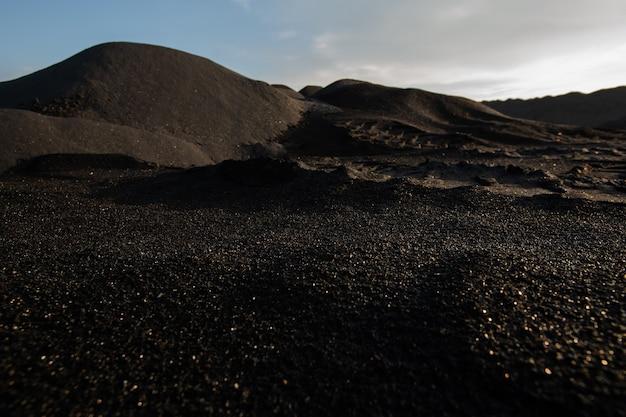 Colline di terreno scuro inquinato, sterile e tossico su un vasto territorio con una cattiva situazione ambientale con cielo nuvoloso sopra che illustra la desolazione