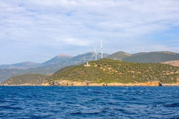 Costa greca collinare del golfo di corinto in una giornata di sole. vecchio edificio del faro e molti parchi eolici