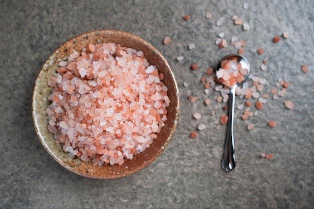 Sale rosa dell'himalaya in una ciotola sul tavolo. vista dall'alto sale rosa con copia spazio.