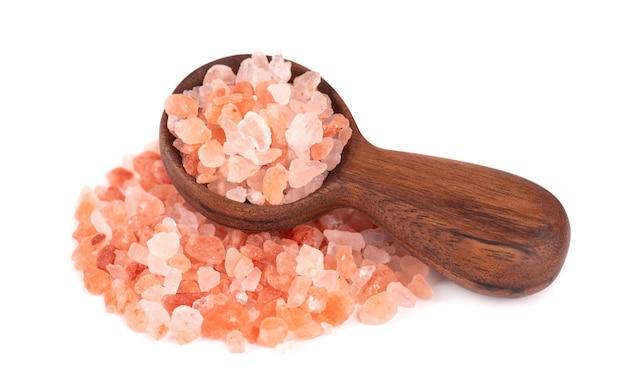 Sale rosa himalayano in cucchiaio di legno, isolato. sale rosa himalayano in cristalli.