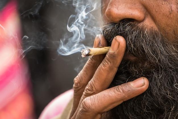 Sadhu indù che fuma marijuana, chiamata localmente ganja, forma di cannabis sativa. consumatore di tabacco. fumatore indugia narcotico fumo stupefacente da sigari fatti in casa. sigaretta da vicino. restringimento degli oppiacei.