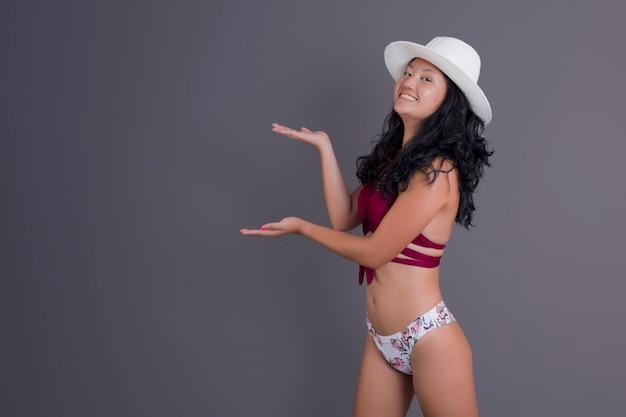 Donna cinese in bikini che indica qualcosa accanto a lei sorridendo e guardando dritto davanti a sé