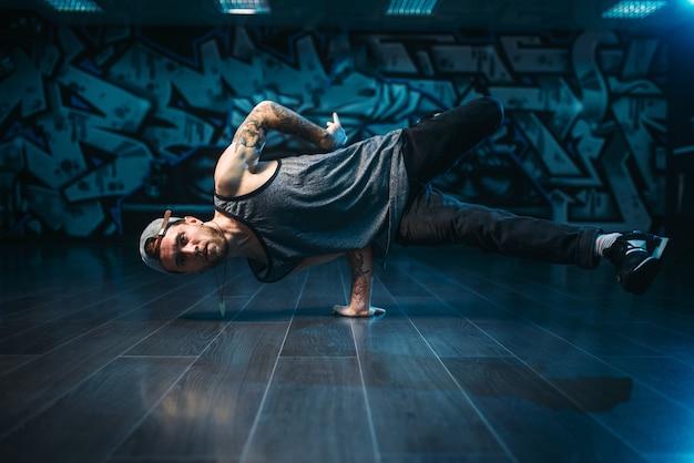 Azione hip-hop, movimenti di ballerino maschio in studio di danza. stile di ballo urbano moderno