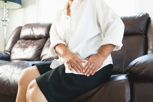 Dolore all'anca della donna anziana a casa, problema sanitario del concetto senior