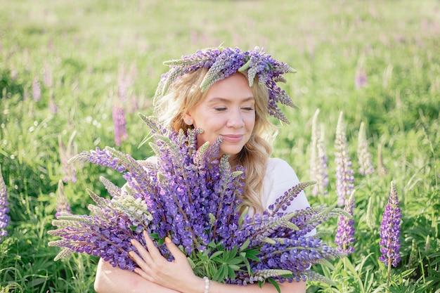 Una ragazza hippy con un mazzo di fiori di campo tra le mani ragazza ha nascosto il viso dietro un mazzo di lupini