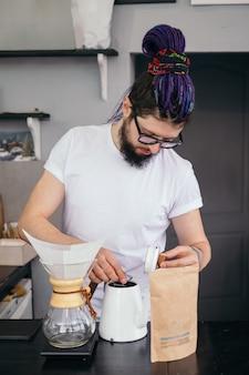 Uomo di barista hipster che produce caffè alternativo