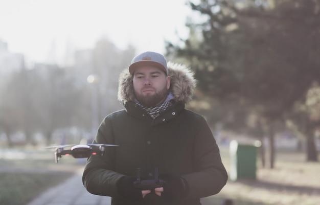 Uomo barbuto hipster in berretto con drone volante all'aperto