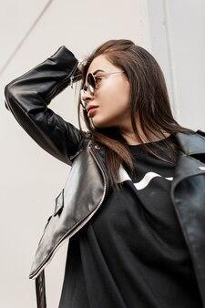 Hipster bella donna fresca con occhiali da sole alla moda in giacca di pelle rock alla moda e felpa nera su sfondo grigio passeggiate in città. ritratto urbano di una modella