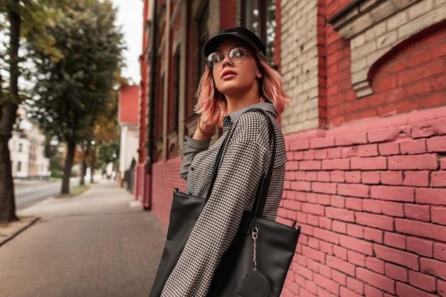 Hipster bella giovane donna con gli occhiali e un berretto in abiti giovanili alla moda con una borsa cammina in città vicino a un edificio in mattoni d'epoca