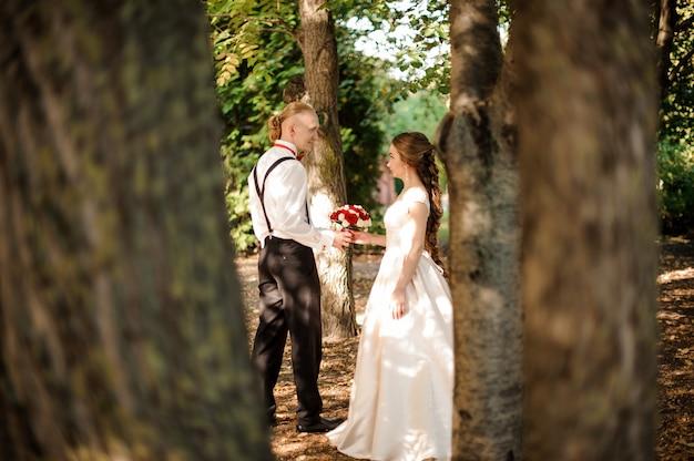 Sposa e sposo hipster che camminano nella foresta tra alberi verdi in una calda giornata estiva